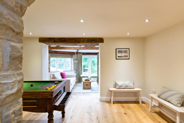 View from the billiards table room through to a light living space