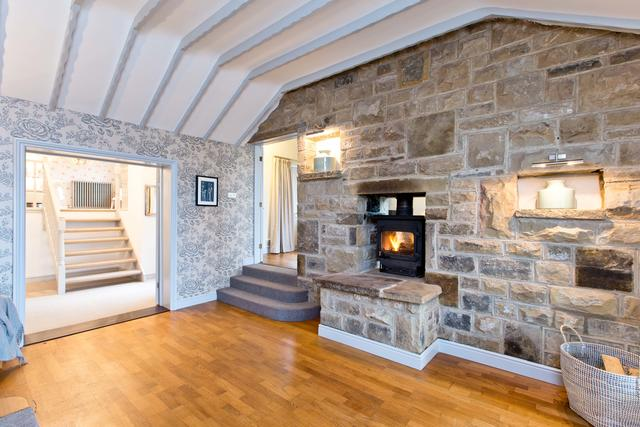 Spacious entrance hall with log burner and view of bedroom one