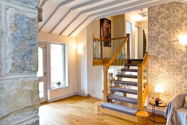 Spacious entrance hall with log burner and view of split level floors